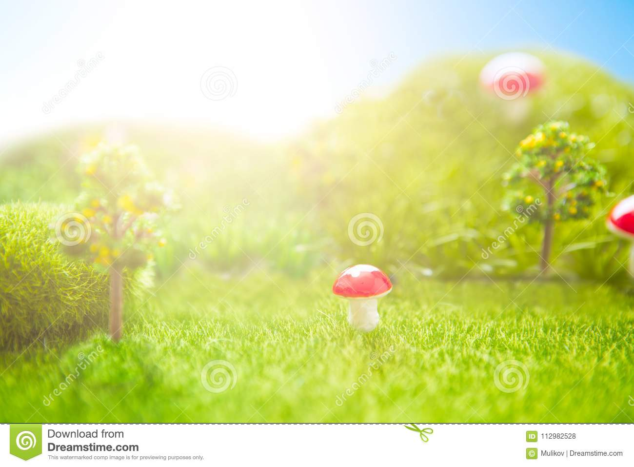 Toy Landscape. Sunset on the plastic green field with plastic grass, mushrooms and trees. Fake grass. Macro