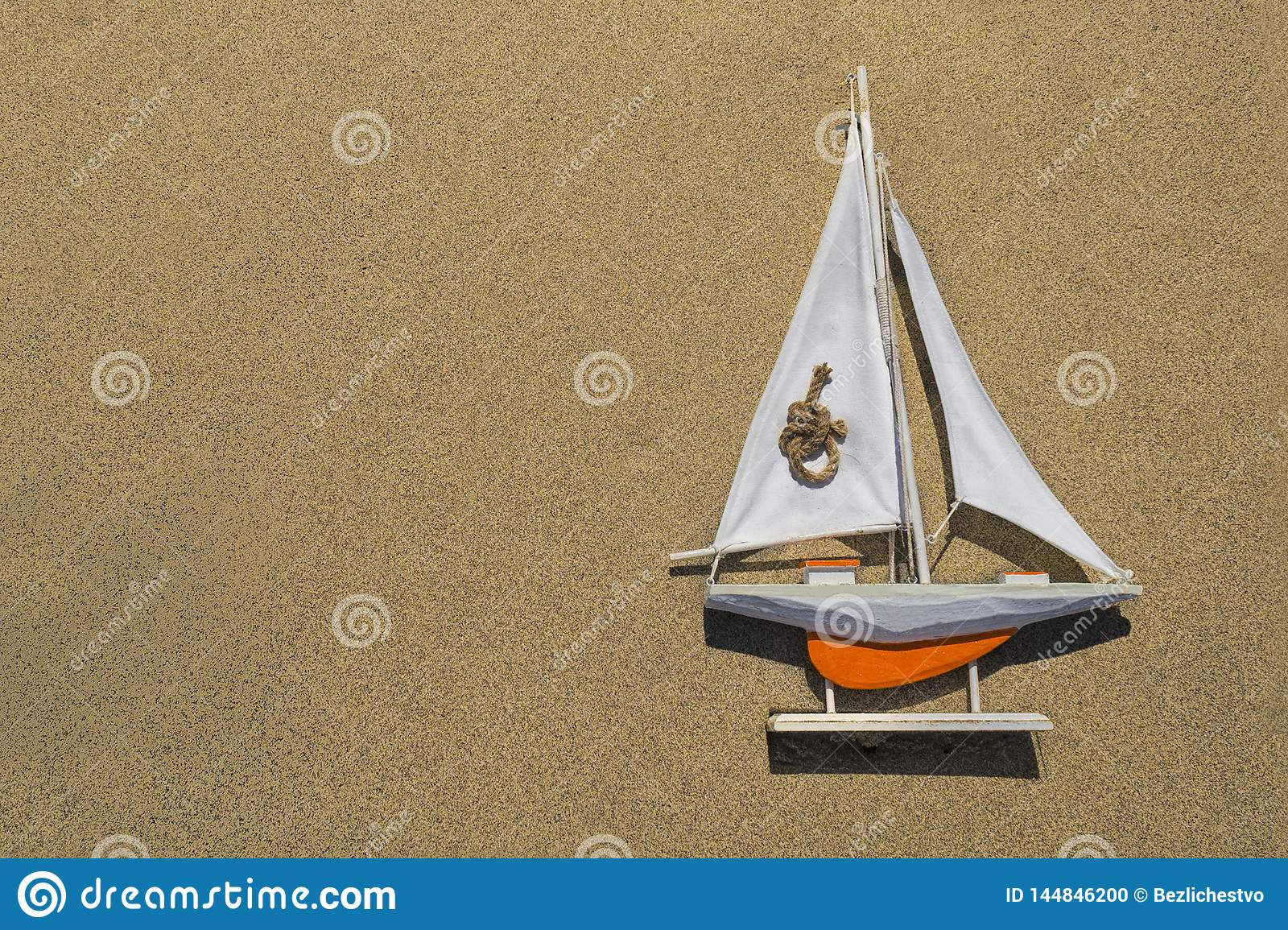 A toy orange ship with a white sail is lying on the textured sand on the right