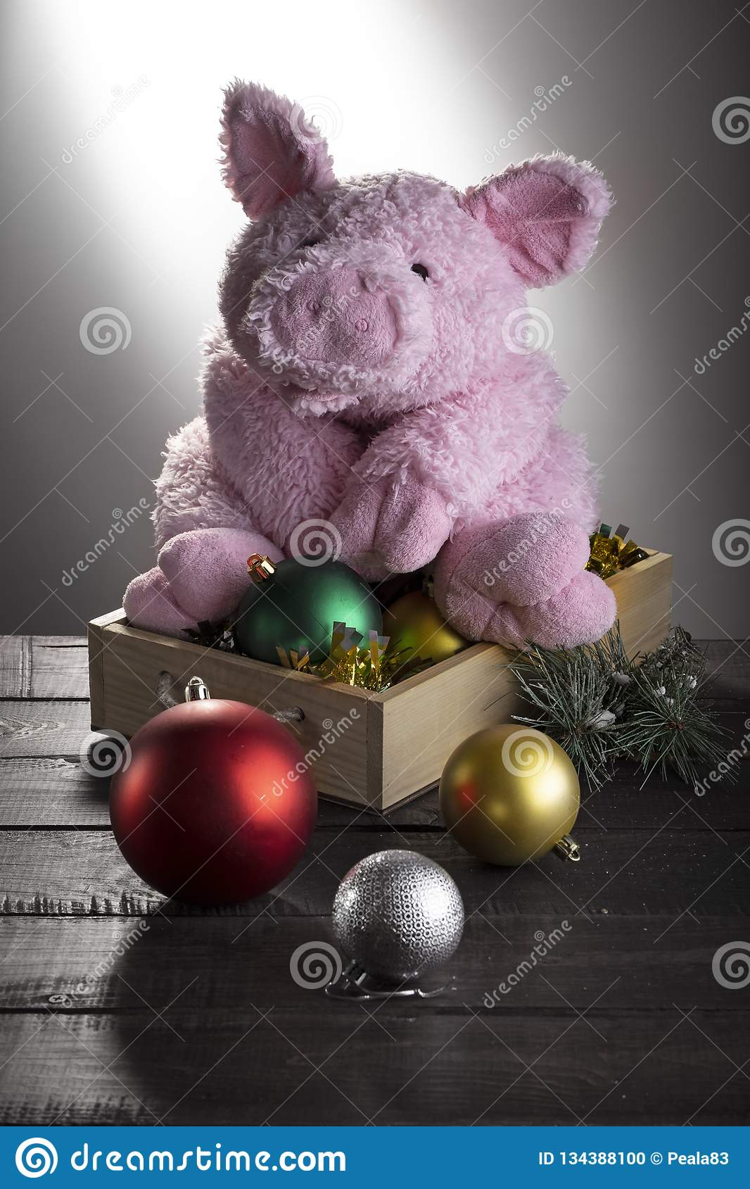 Toy pig sitting on box with New year balls on wooden surface. Festive card, Chinese New Year of Pig, Zodiac symbol 2019