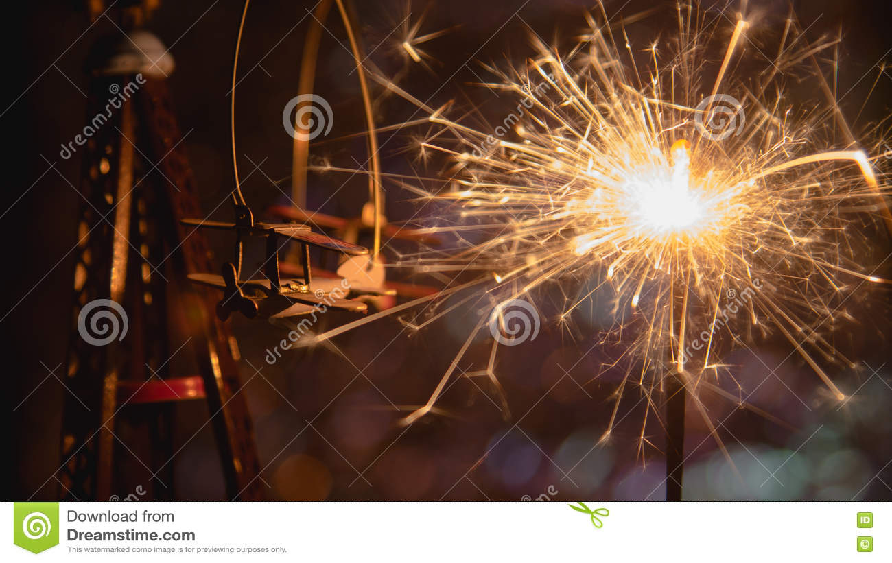 toy plane with new year party sparkler and abstract circular bokeh background christmas lights