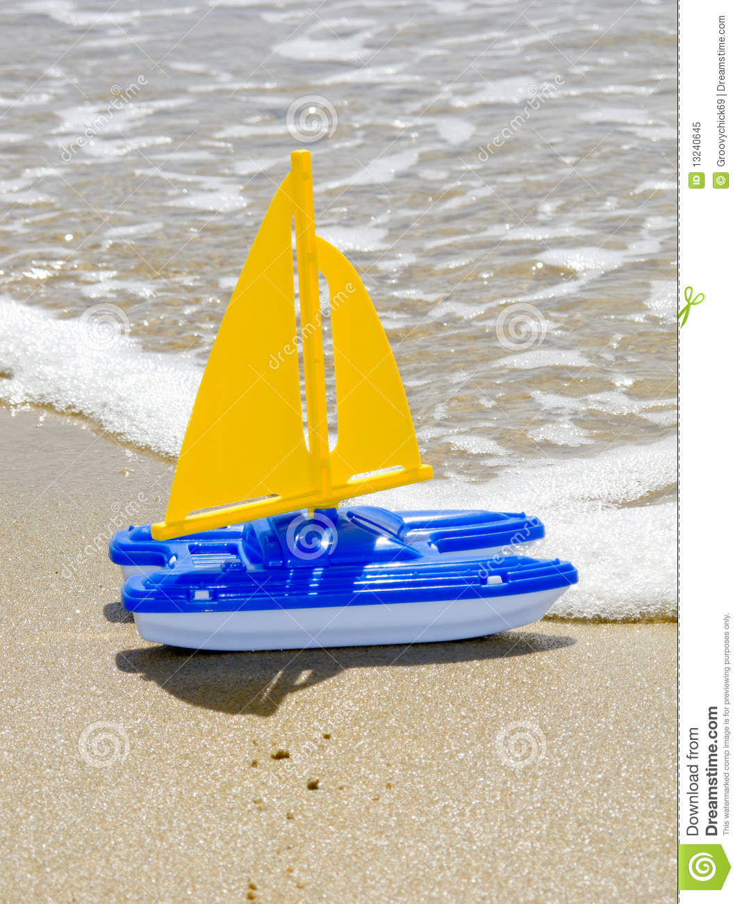 This is a photograph of a toy sailboat on the sandy beach of Newport ...
