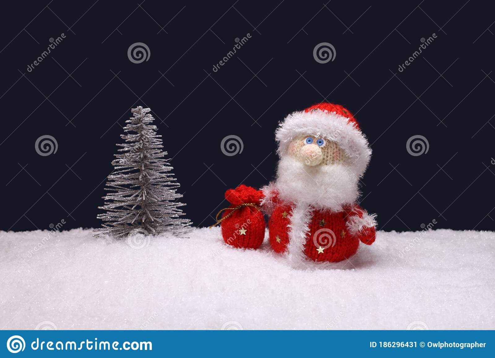 Toy Santa Claus Is Standing Next To A Toy Silver Christmas Tree On Artificial White Snow Against Navy Blue Background Stock Image Image Of Greeting Claus 186296431