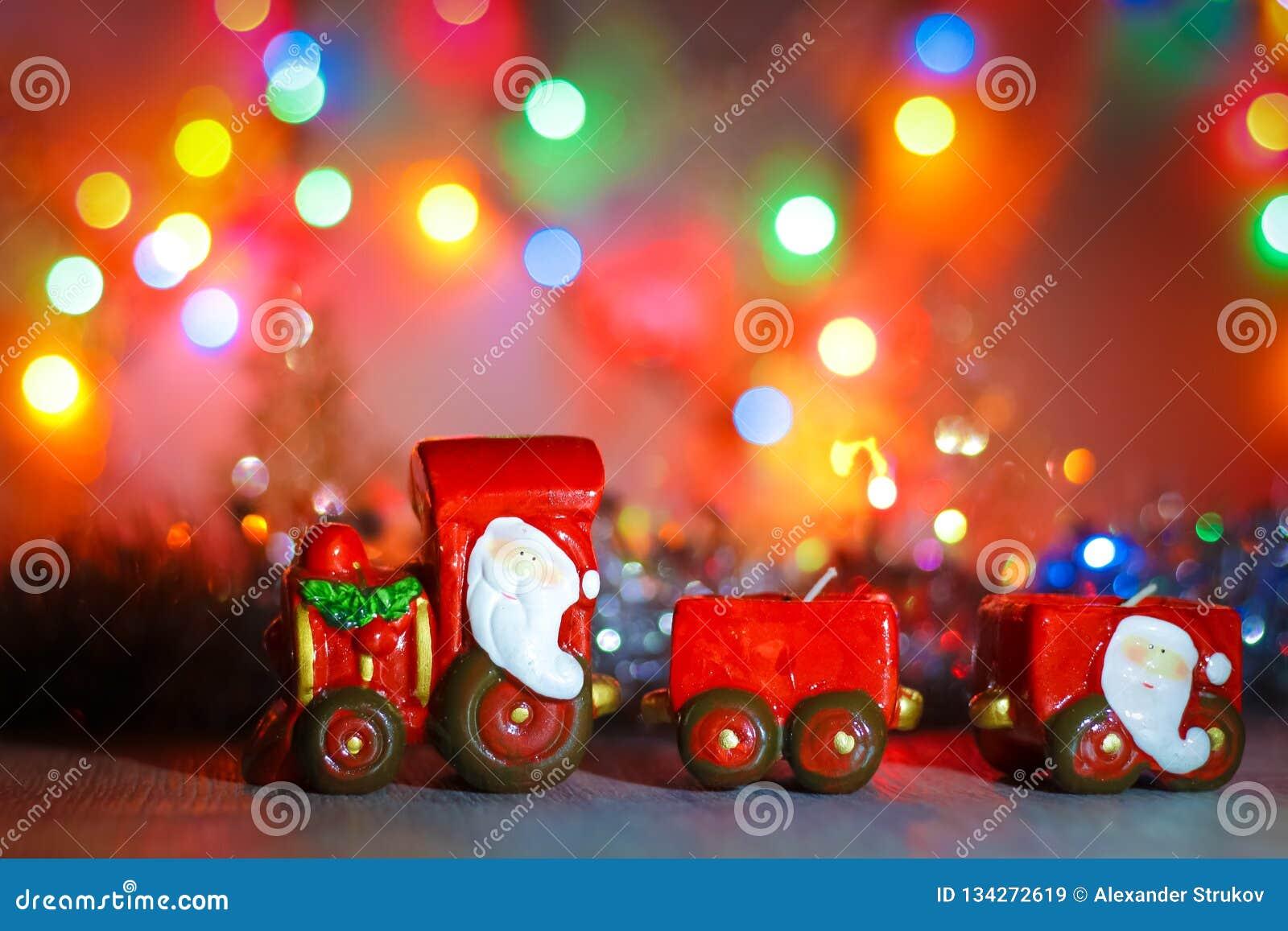 Toy Steam Train met Santa Claus bij een achtergrond van gouden slingers en het onduidelijke beeld van gekleurde lichten