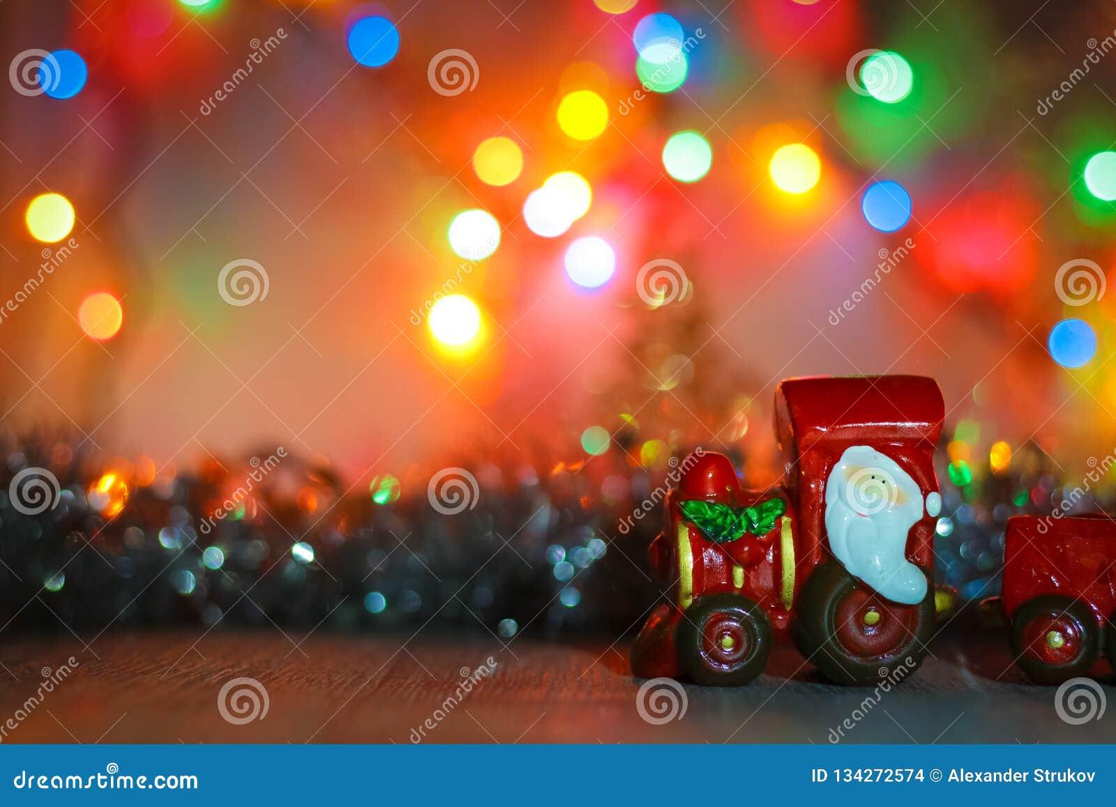 Toy Steam Train mit Santa Claus auf einem Hintergrund von goldenen Girlanden und Unschärfe von farbigen Lichtern