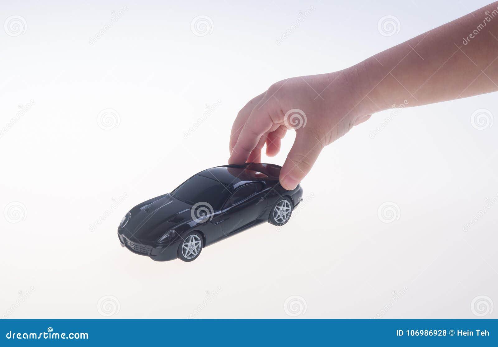 Toy stuk speelgoed auto met hand op de achtergrond