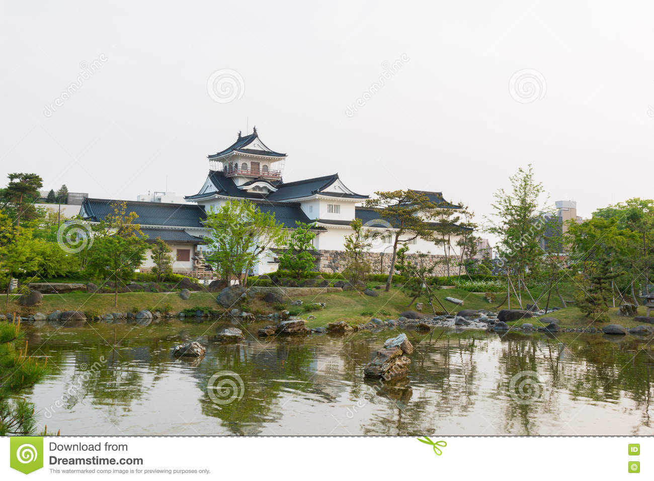 Toyama castle with beautiful garden and reflection in water.