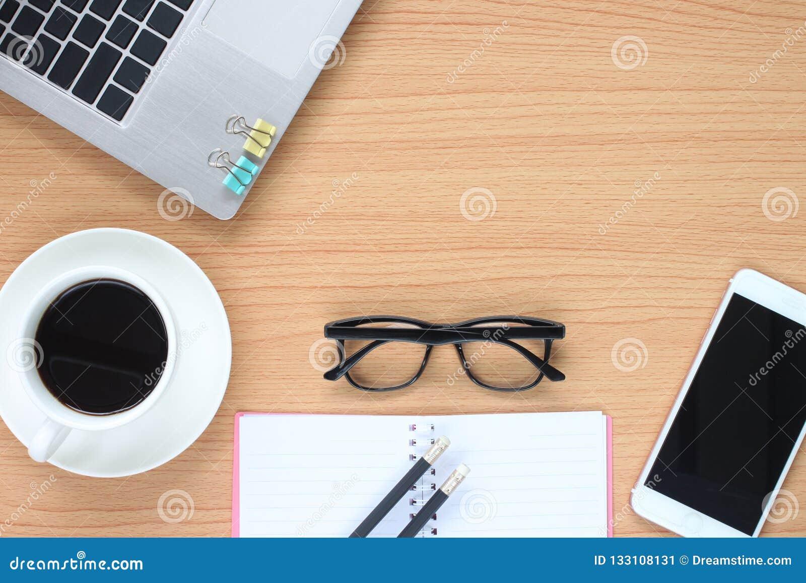 Träarbeta för tabell har en bärbar dator, och kaffe rånar nära för att bua