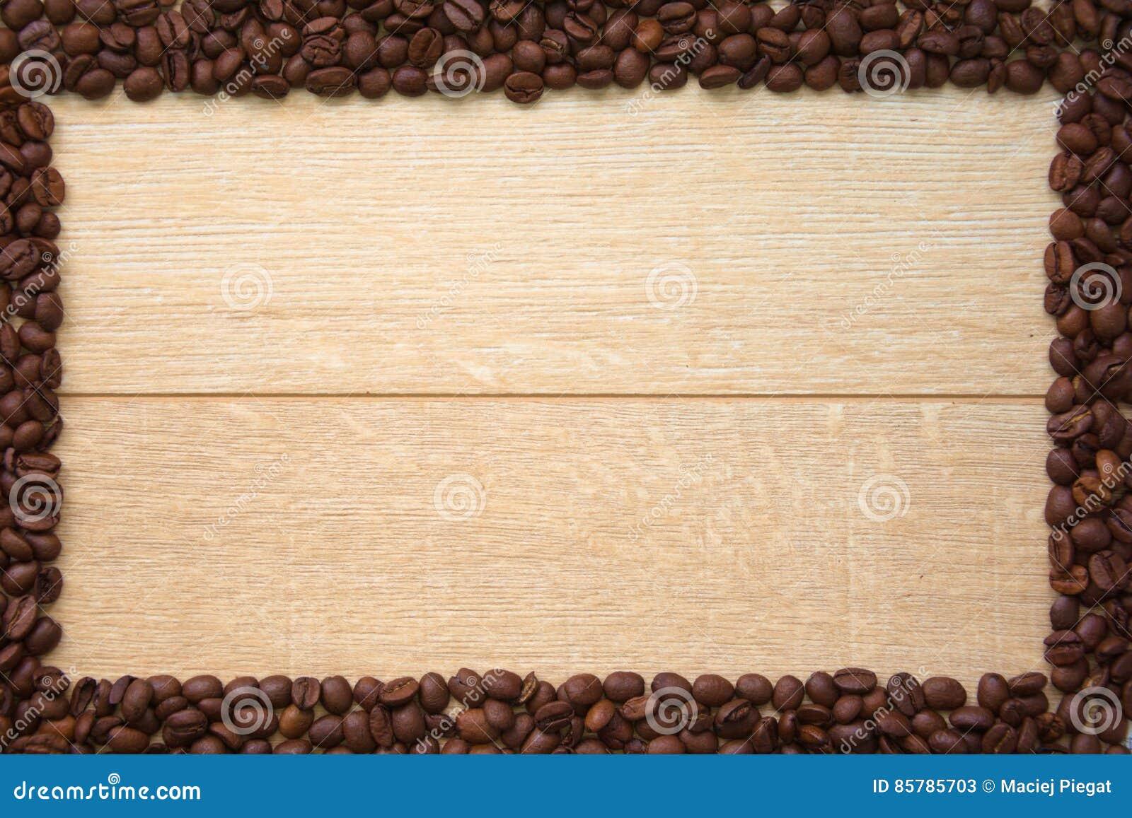 Träbakgrund med ramen av kaffebönor
