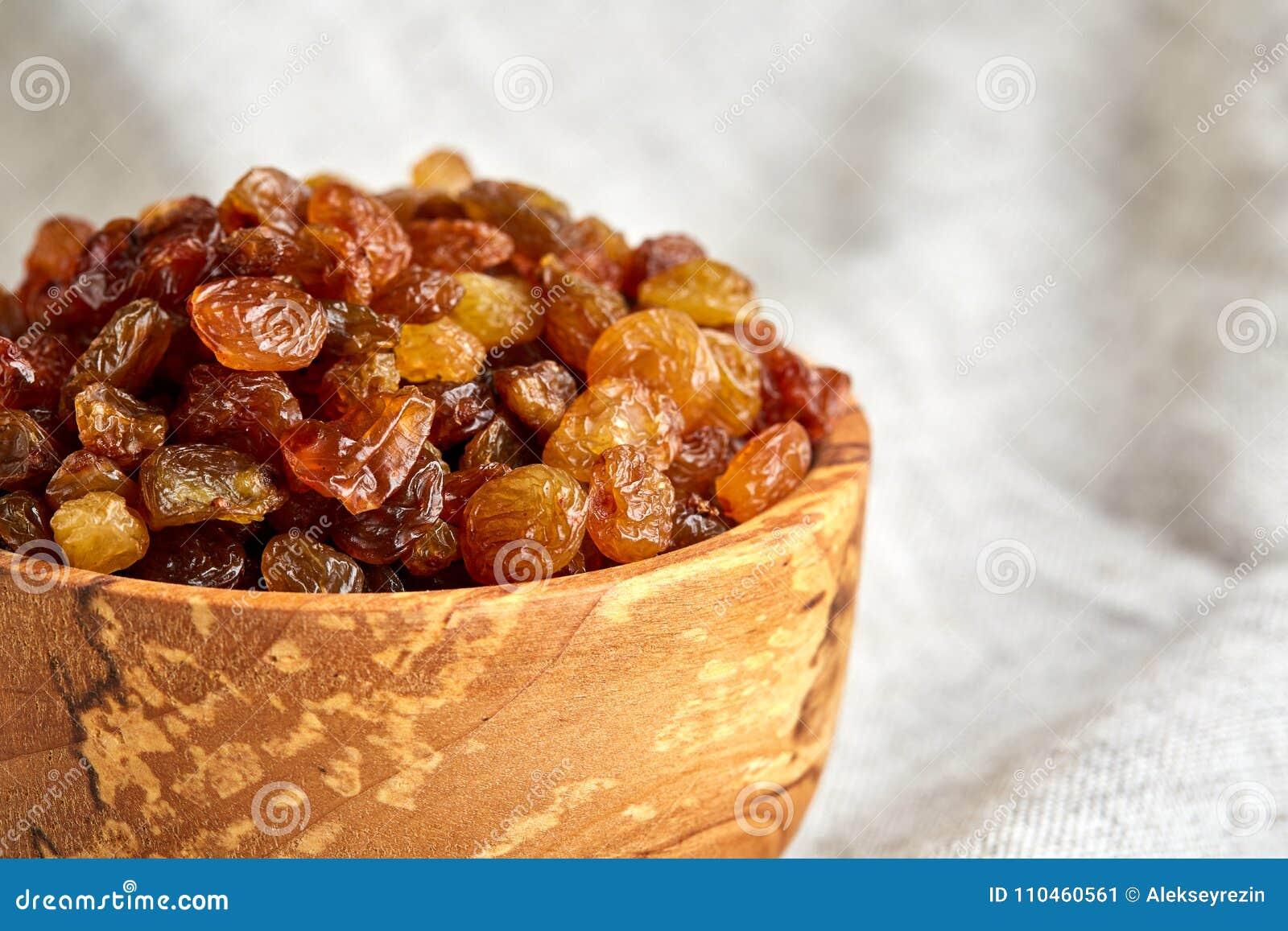 Träbunke med guld- russin på den ljusa bordduken, närbild, selektiv fokus