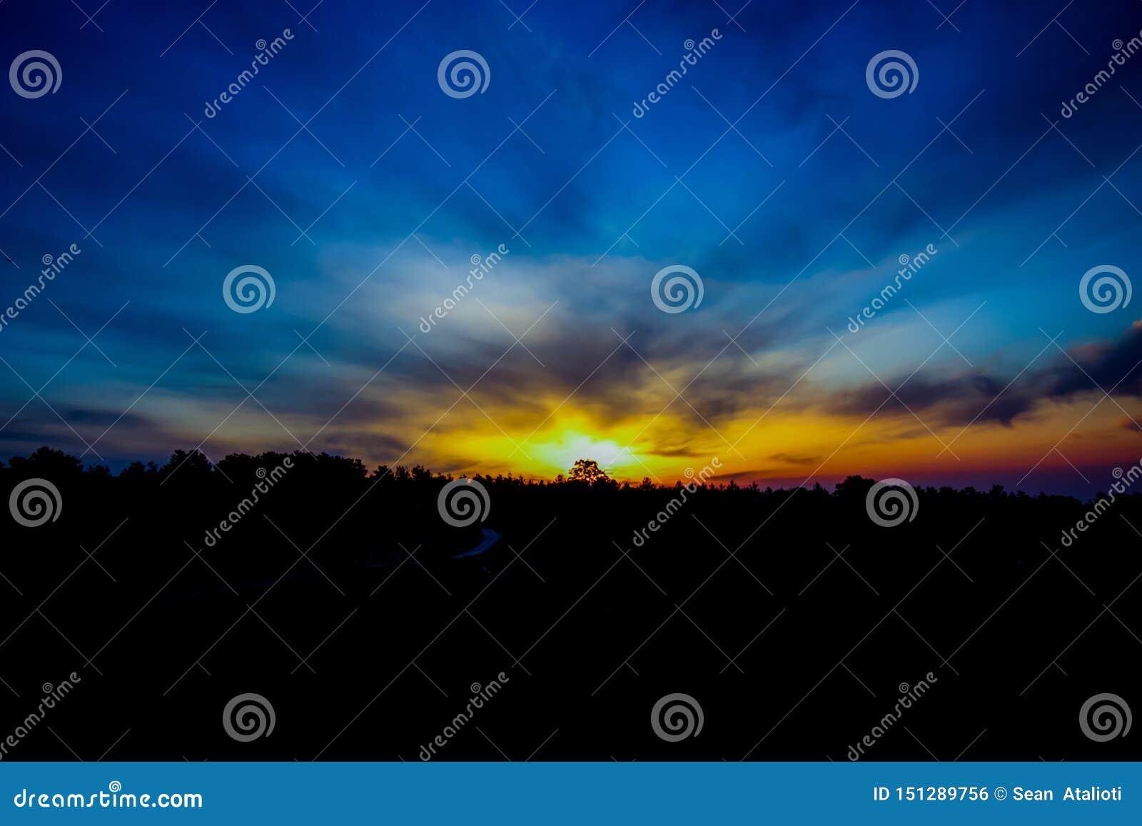Träd för horisonten, bergsoluppgång i morgonhimlen, vidsträckta färger av solen över bergen, grekisk sollöneförhöjning