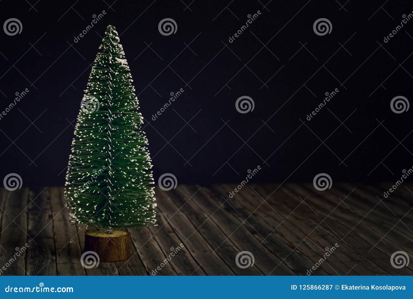 Träd för nytt år på bakgrund för mörk svart och trä