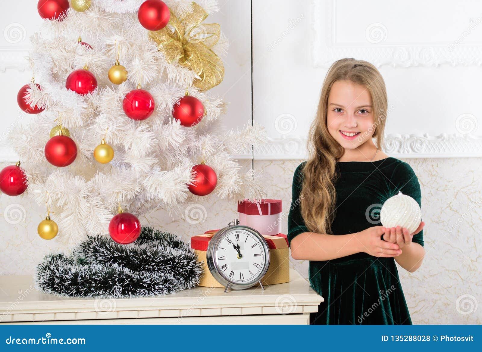 Träd för ungeflickajul som väntar den midnatta klockan Barndomlyckabegrepp Barnet firar jul hemma favorit