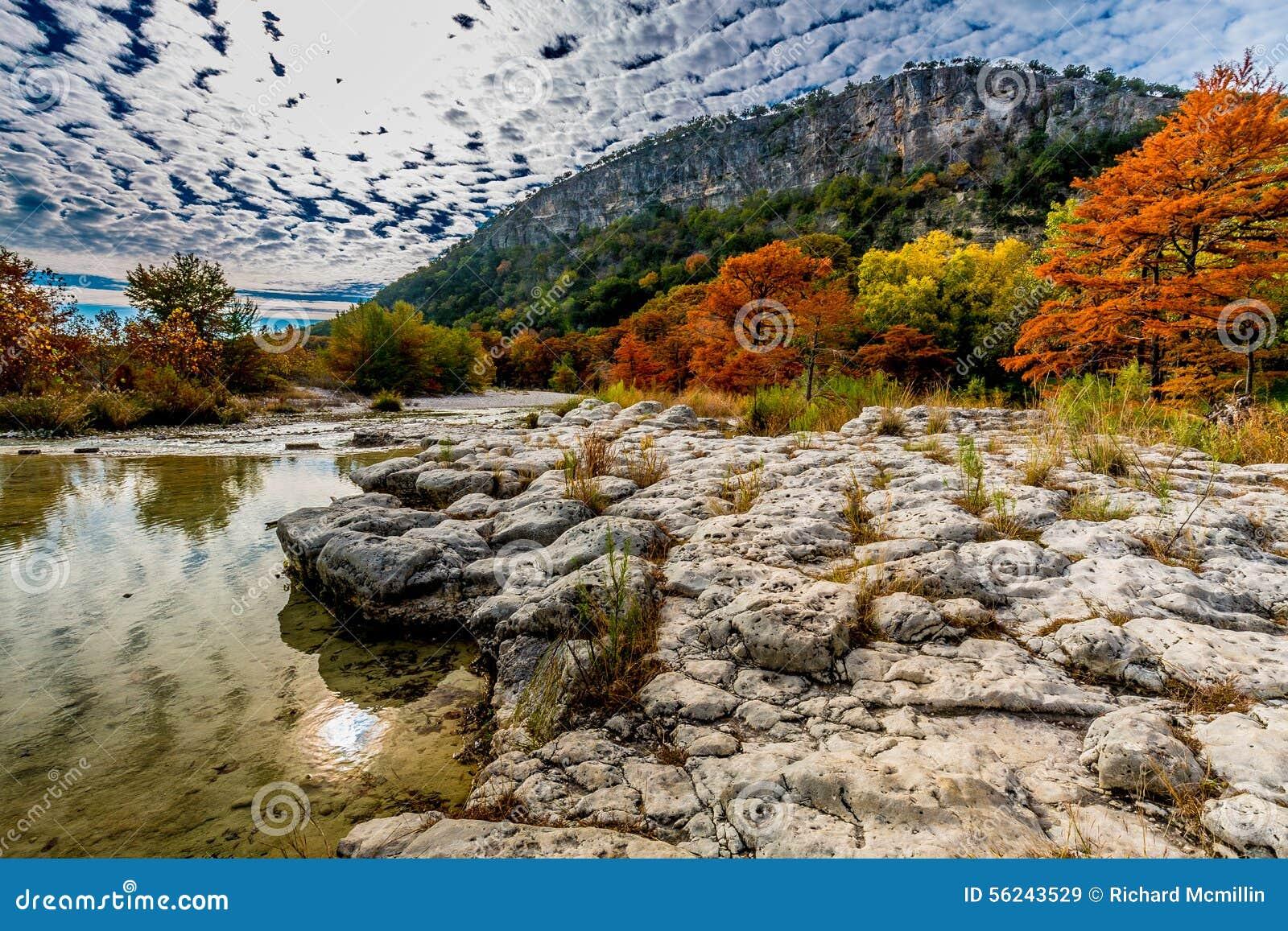 Träd med nedgånglövverk på en Rocky Bank av den Frio floden med kullen i bakgrund