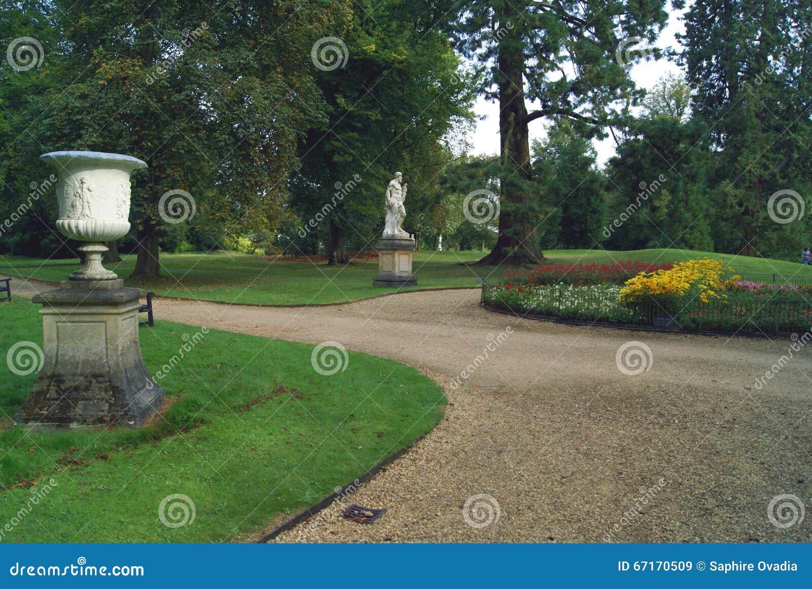 Trädgårds- bana med en prydnad och en romarestaty på en sockel
