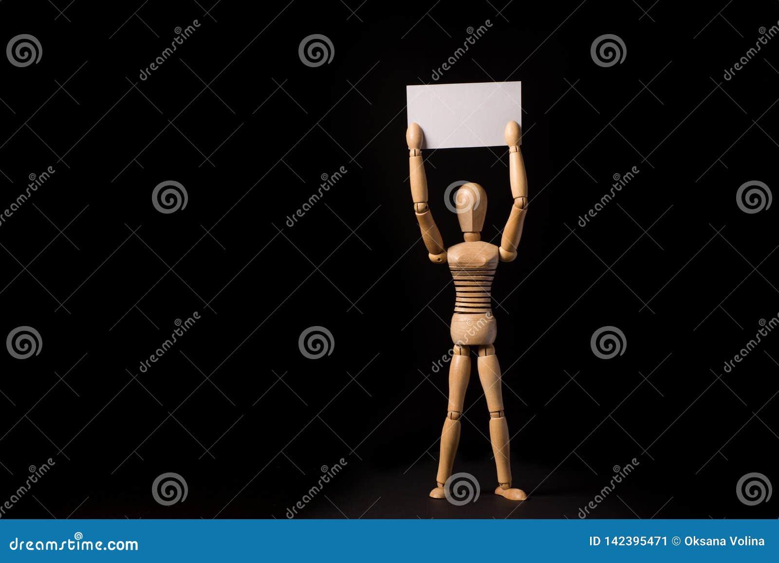 Trädocka med en affisch eller baner i deras händer på en svart bakgrund