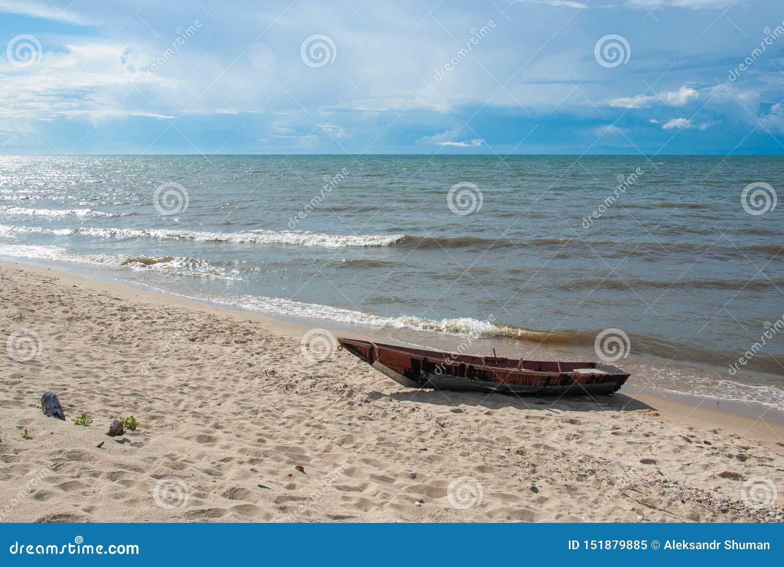 Träfartyg på den sandiga kusten av Lake Baikal, blå himmel och lugna vatten