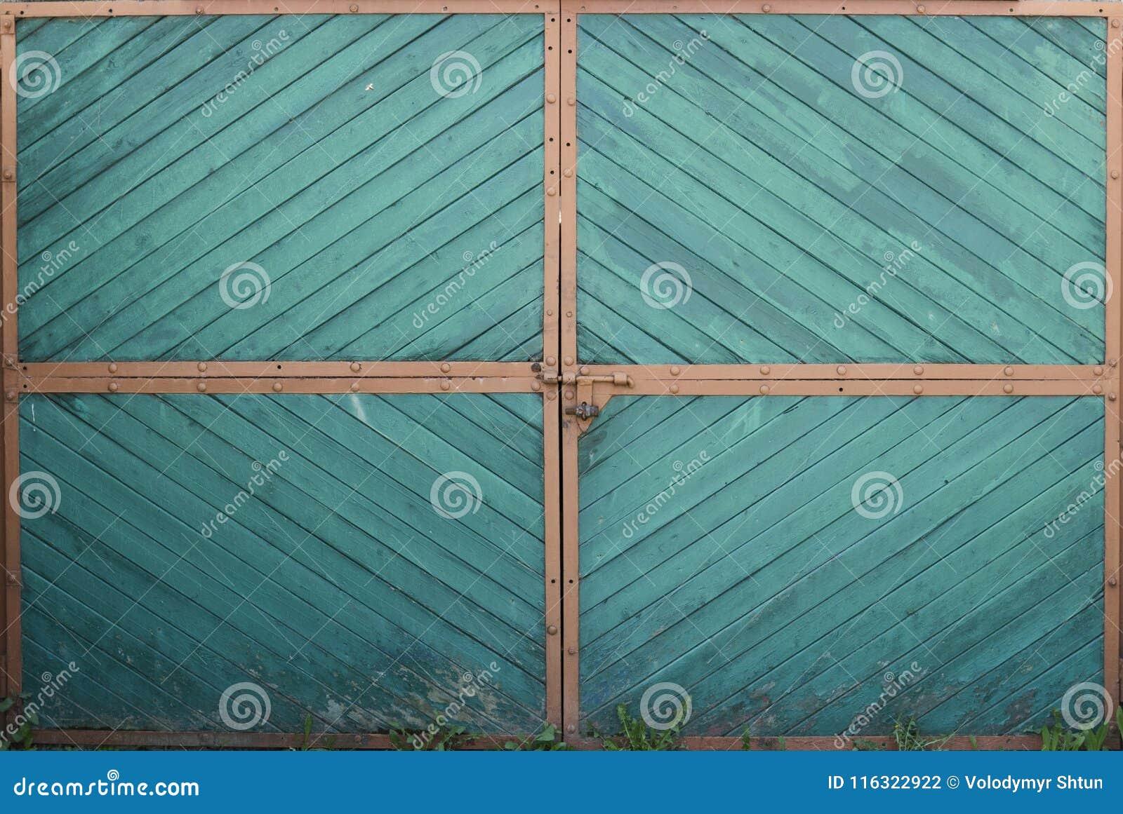 Trägrön portdörr med apelsinhörn och gräs på en jordning