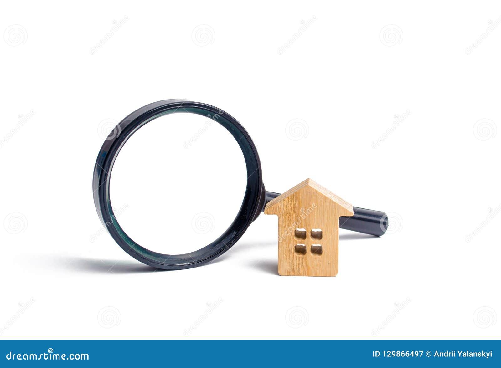 Trähus och förstoringsglas på en vit bakgrund Köpa och sälja fastigheten, byggnadsnybyggen, kontor och hem