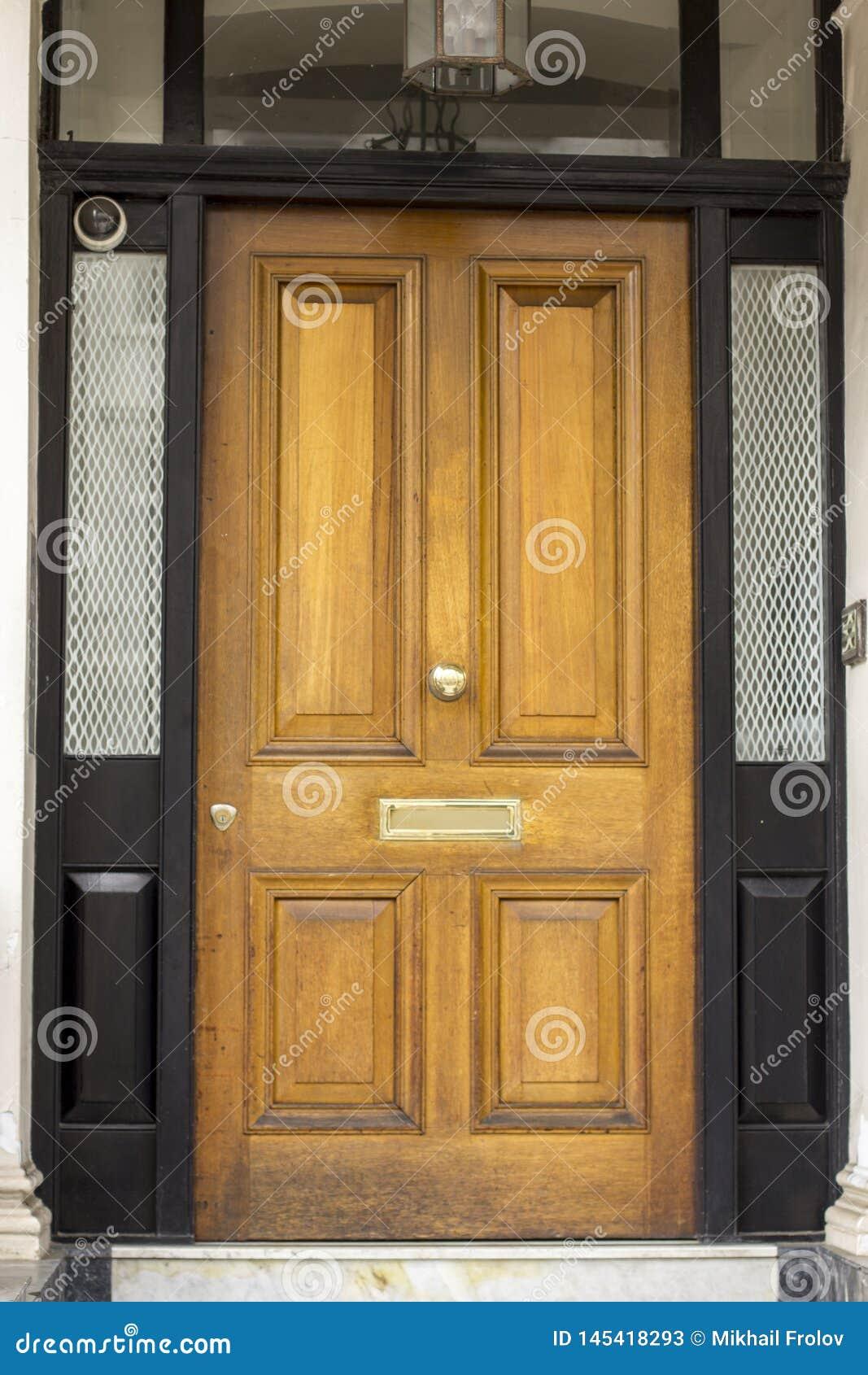 Träingångsdörr till bostads- byggnad i London Typisk dörr i den engelska stilen