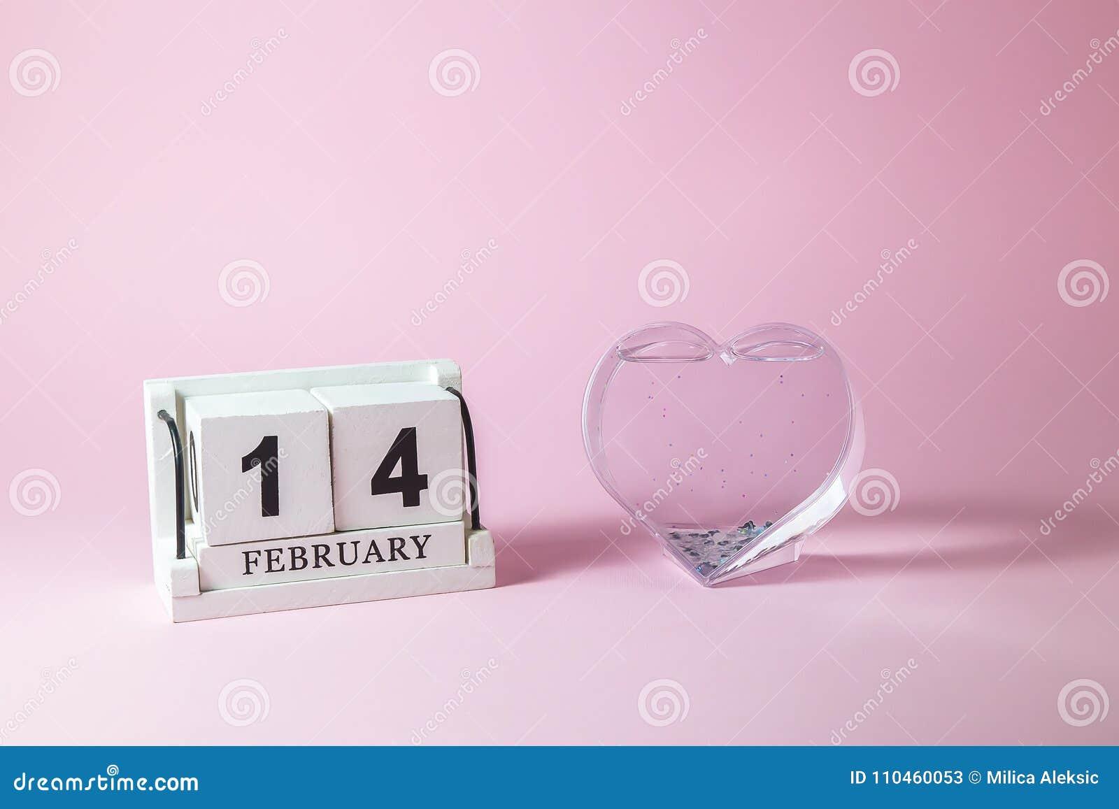 Träkalender med hjärta på den rosa bakgrunden Förälskelse- och valentindagbegrepp
