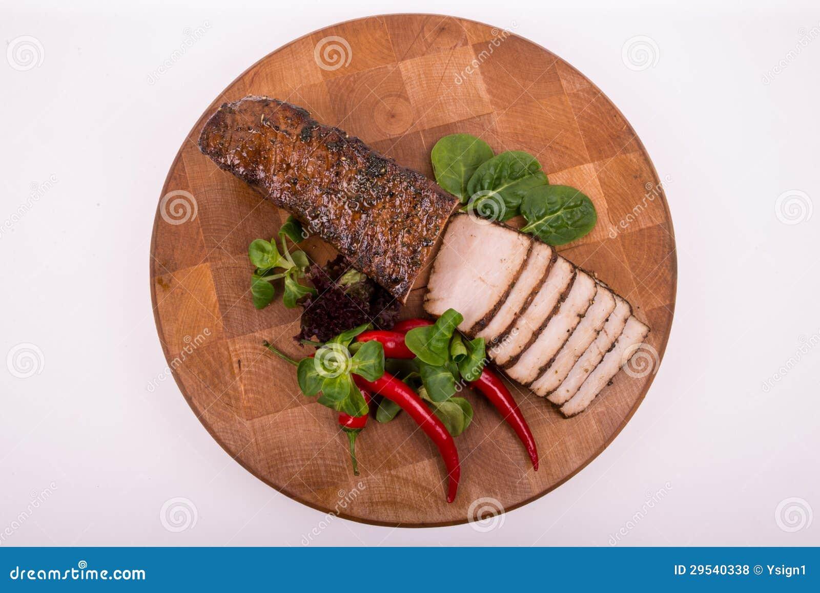 Träskärbräda redondo com ââpork, salada e o pimentão cortados