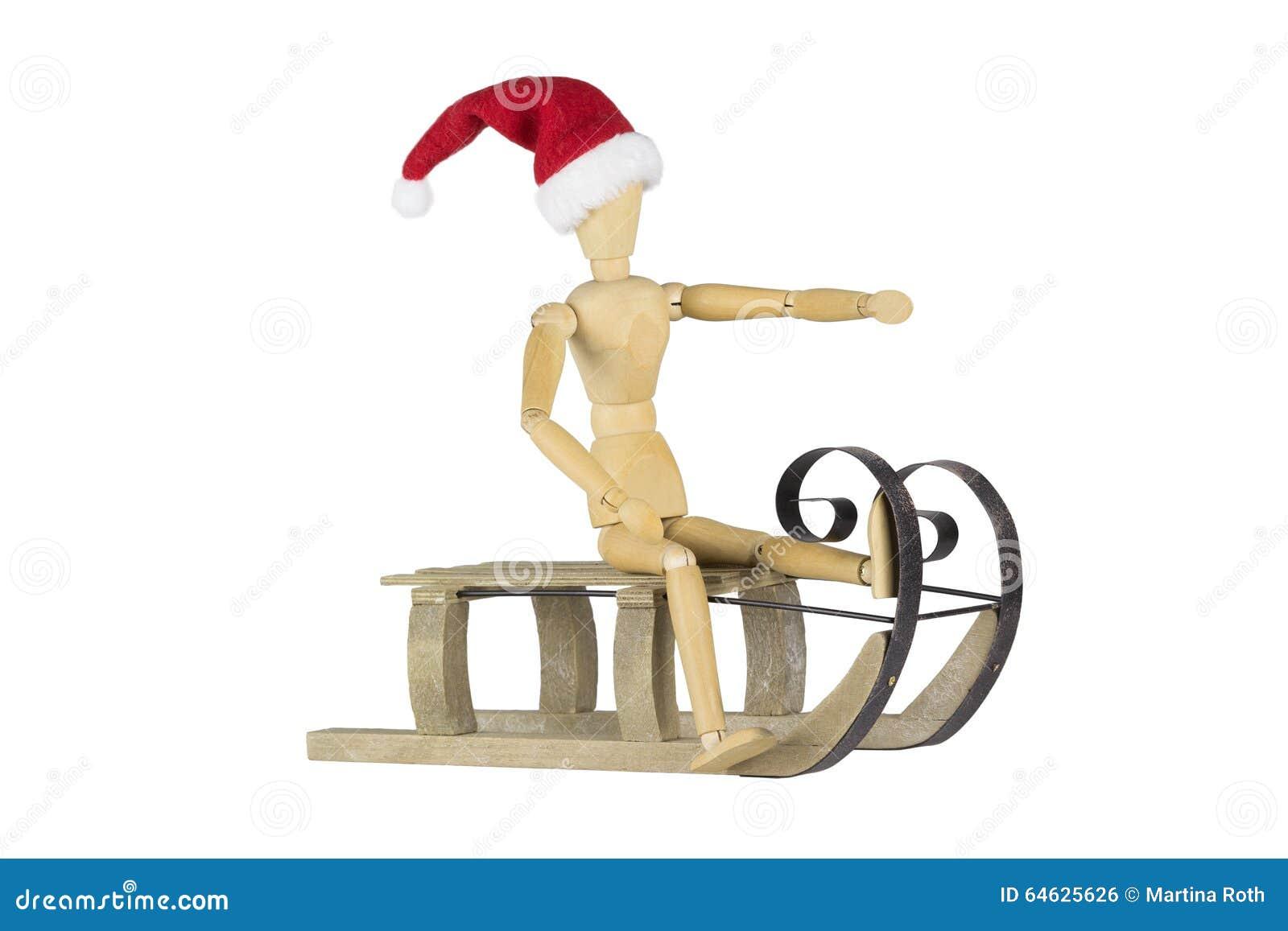 Träskyltdocka på en släde som bär en santa hatt