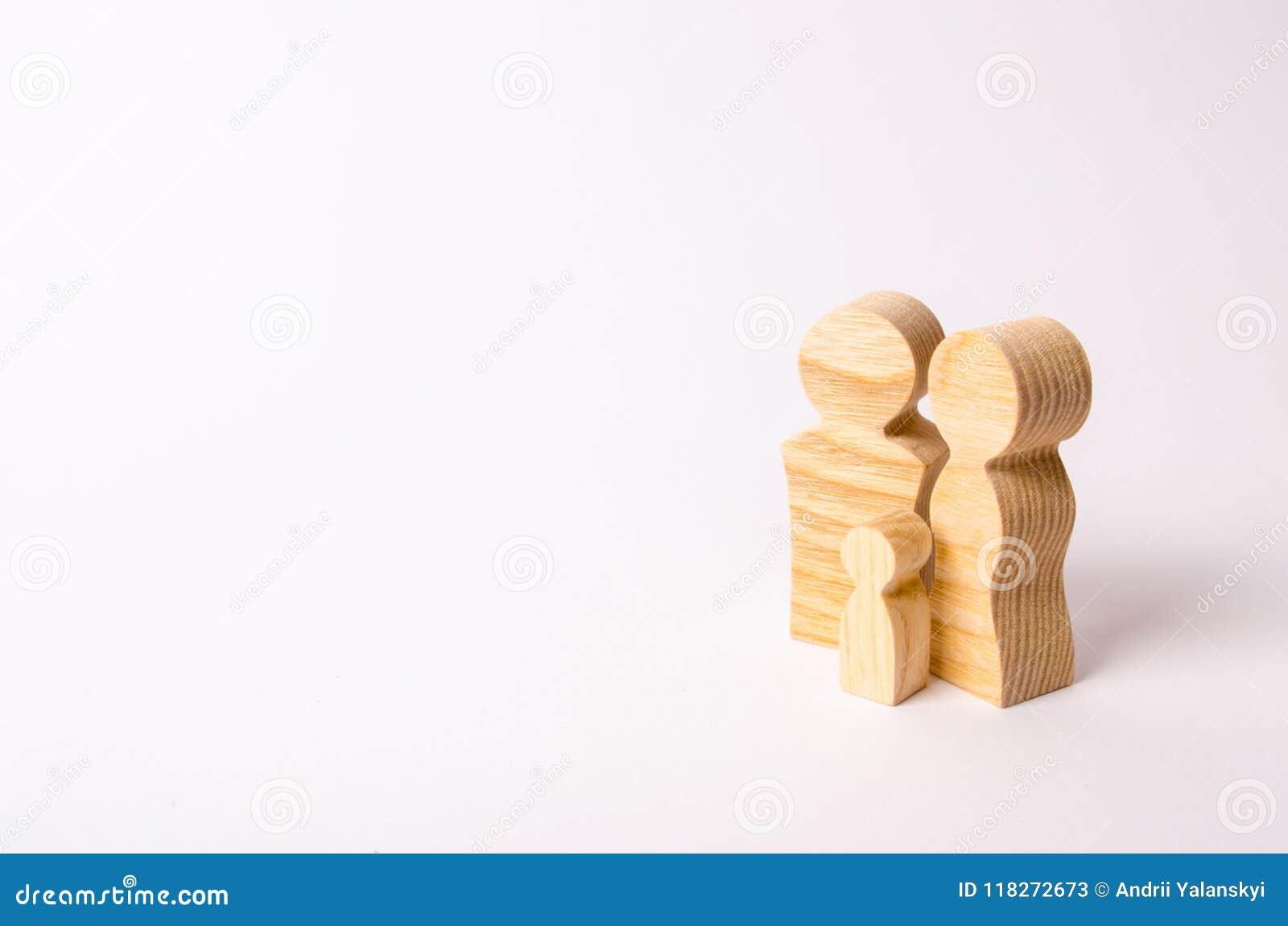 Trästatyetter av en ung familj på en vit bakgrund Begrepp av ett ungt starkt och sunt gift par