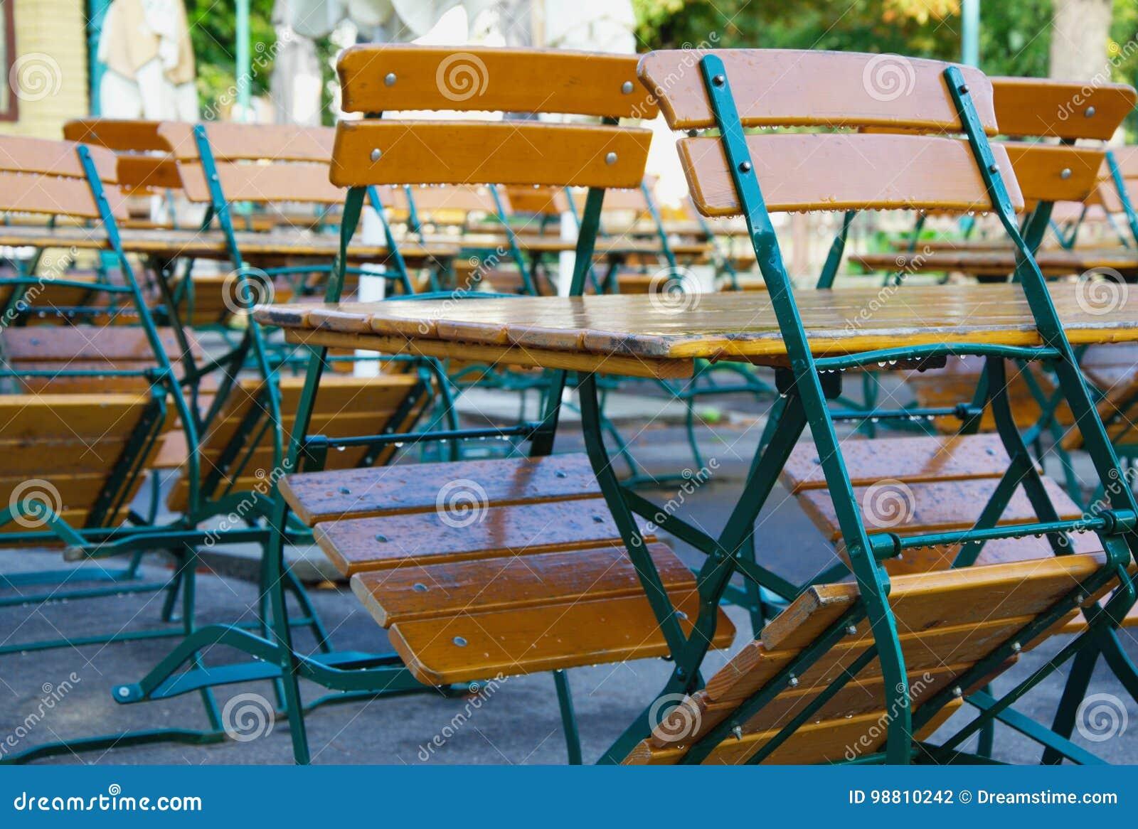Trästolar som lutar på tabeller i stängd kafé eller restaurang under morgonen efter regnet