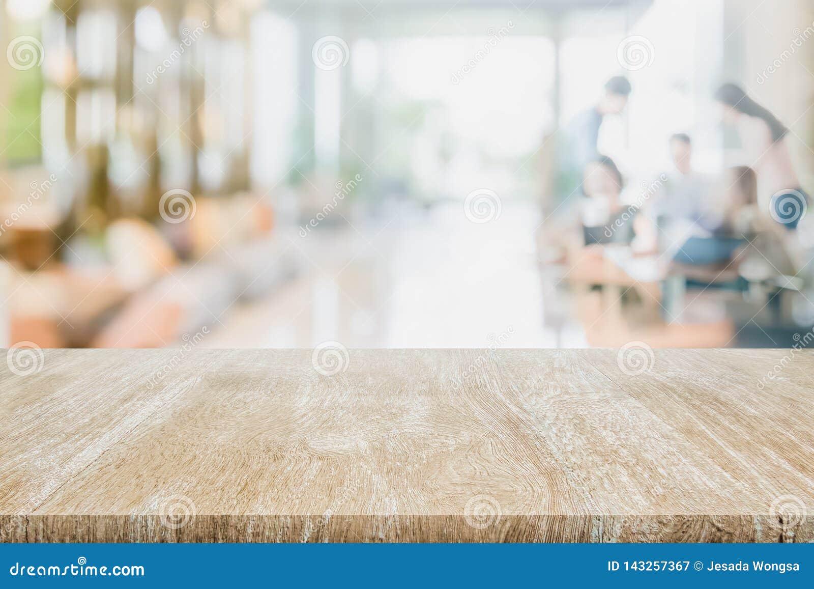 Trätabellöverkanten på suddigt inre suddigt folkmöte i coffee shopkaféCo-arbete utrymme Ready använde oss för att visa eller