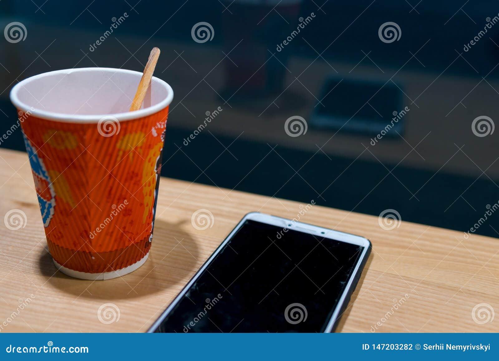 Trätabell i kafét, nattetid, mörkt tema smartphone och te, kaffe begrepp av att prata och att arbeta och att blogging och att lär