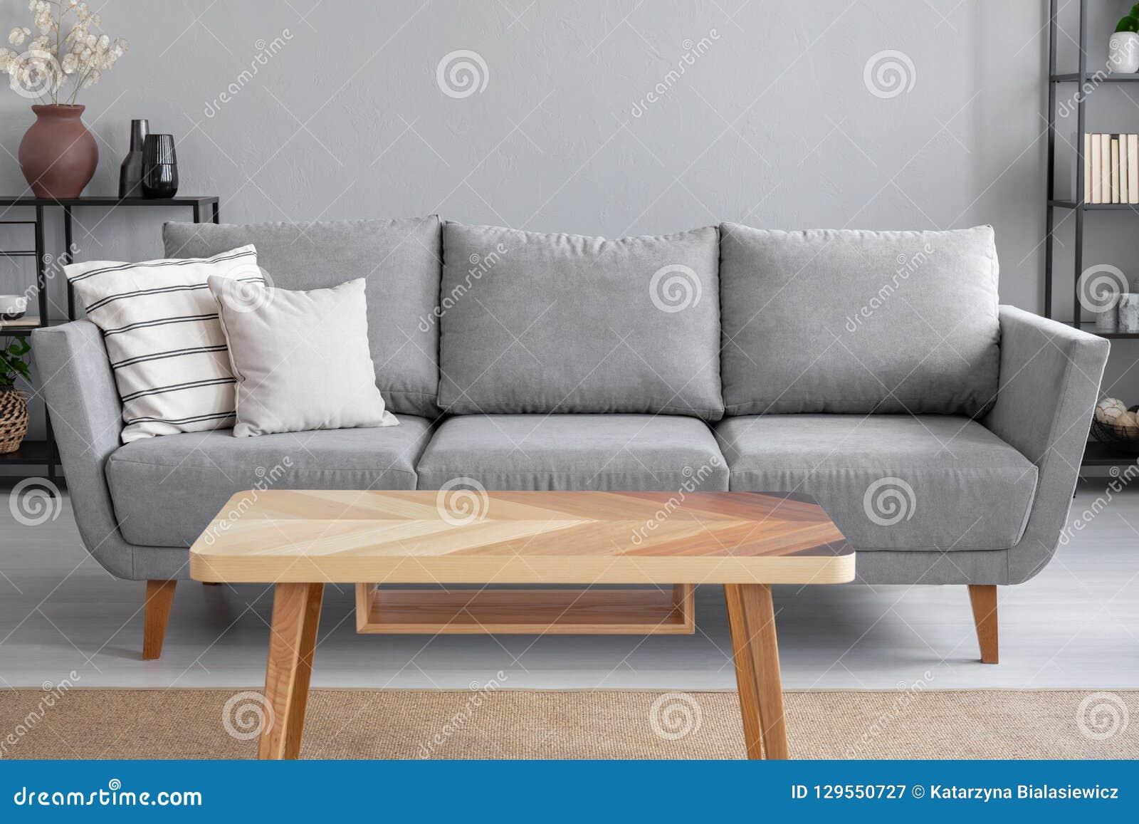 Trätabell och stor grå soffa med kuddar i vardagsrum av den moderiktiga lägenheten, verkligt foto