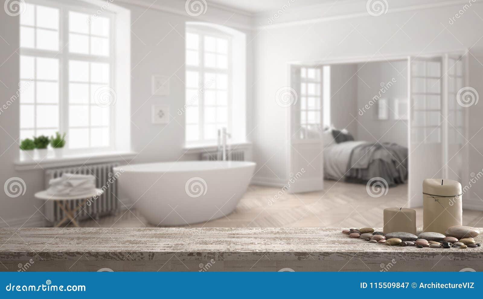 Trätappningtabellöverkant eller hylla med stearinljus och kiselstenar, zenlynne, över suddigt minimalist scandinavian vitt badrum