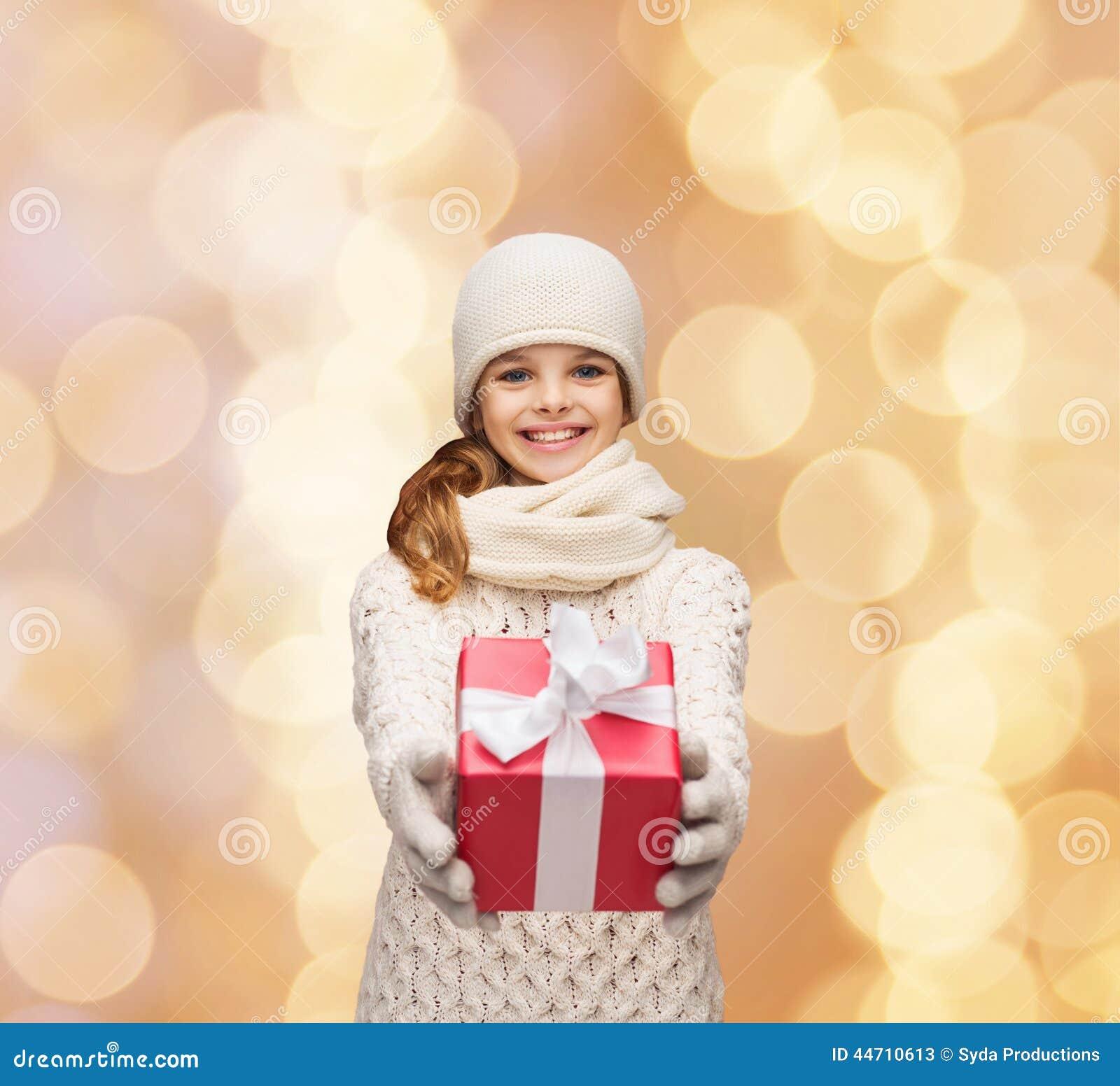 Träumendes Mädchen in der Winterkleidung mit Geschenkbox
