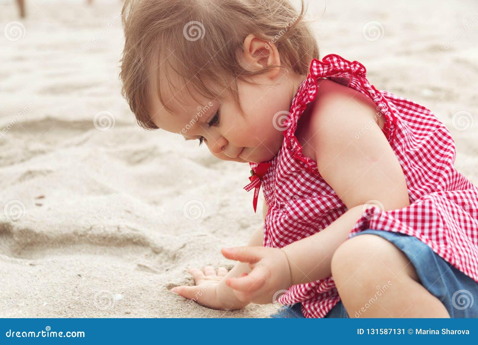 Träumerisches Kind Nettes dunkelhaariges Kinderkleines kleines Kinderbaby, das auf Hinterteilen sitzt und an mit Sand auf Strand