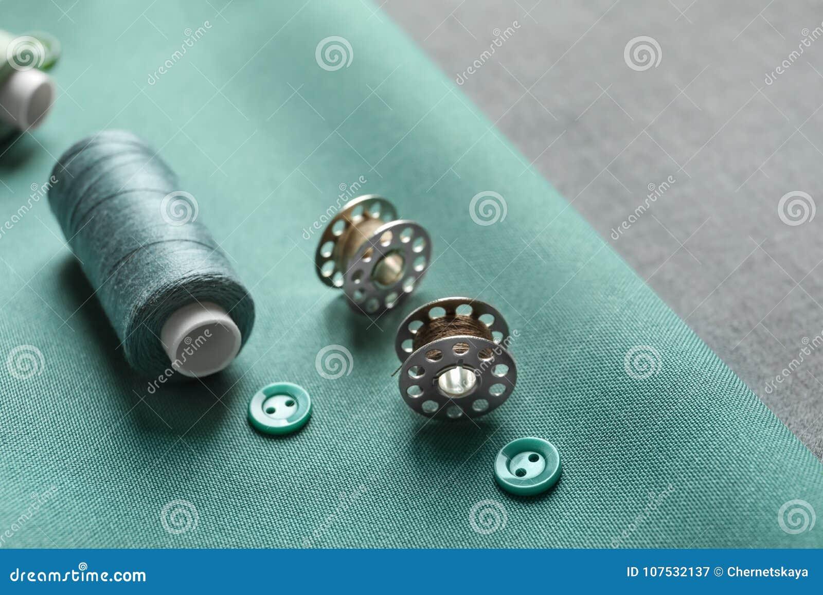 Trådar, knappar och rullar på tyg,
