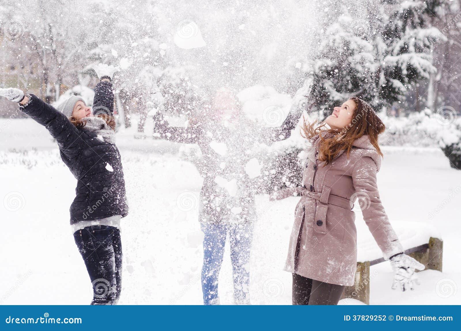 Três adolescentes que jogam a neve no ar
