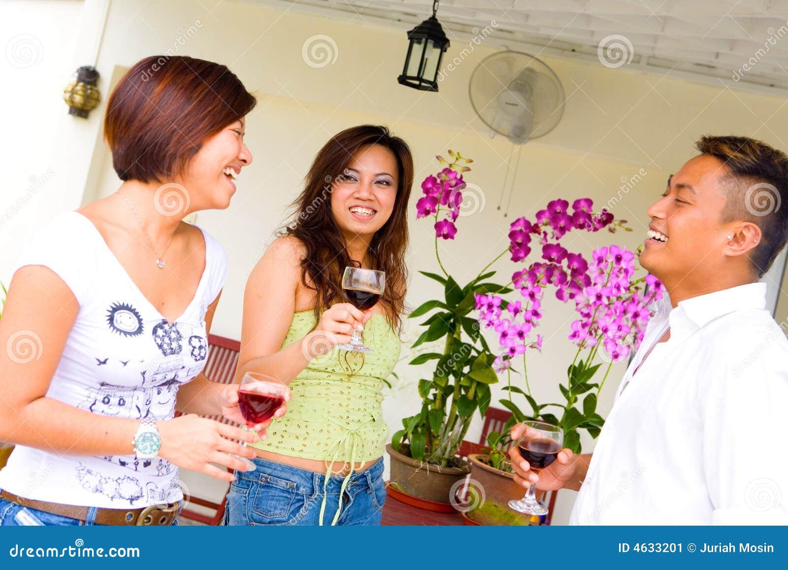 Três amigos asiáticos que socializam