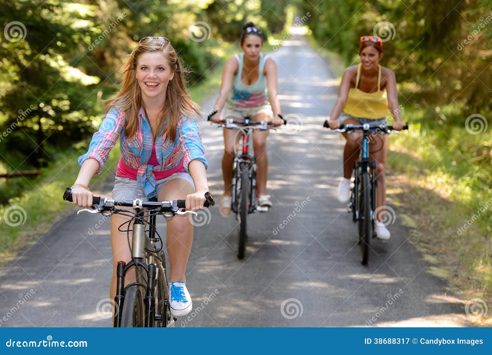 Três amigos fêmeas que montam bicicletas no parque