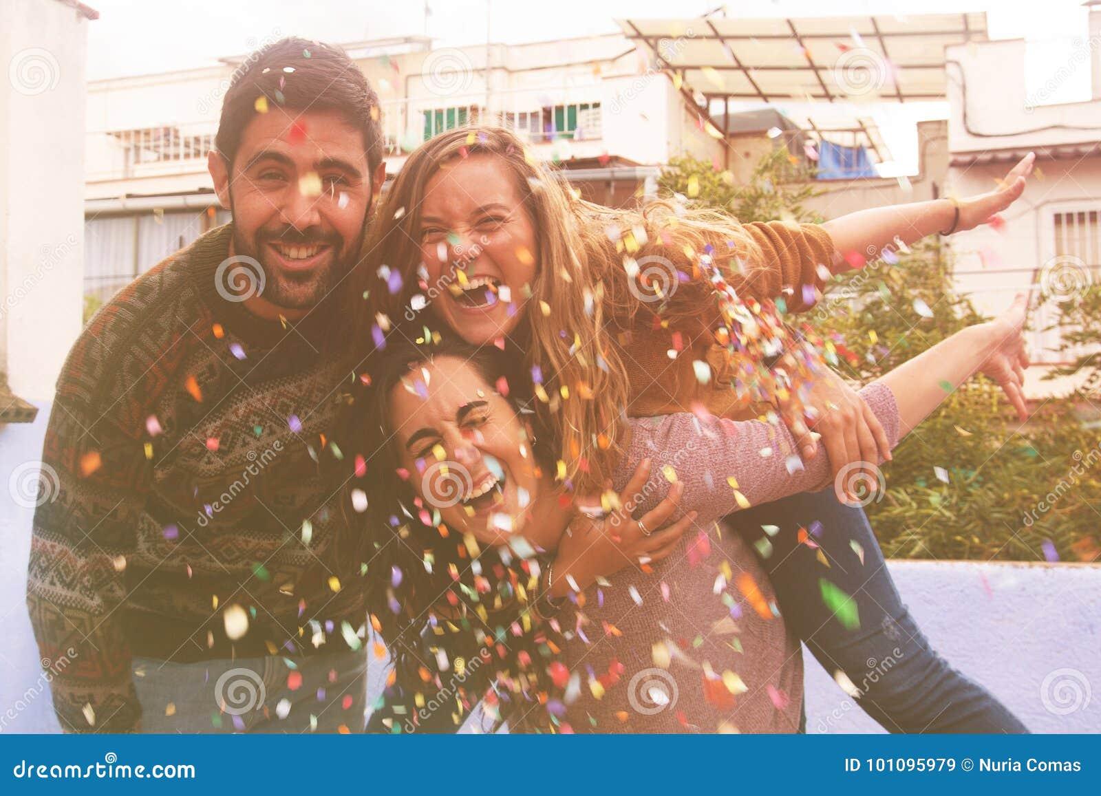 Três amigos muito felizes no partido do telhado e em confetes de jogo