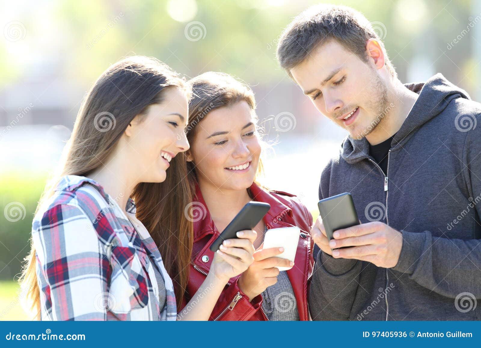 Três amigos que falam guardando seus telefones espertos