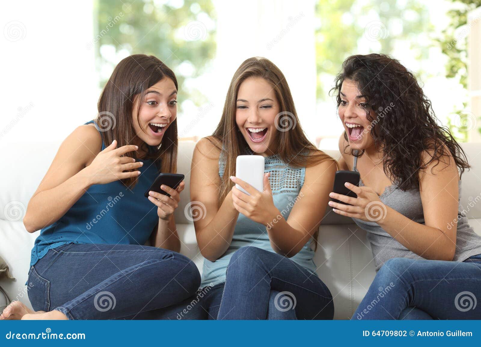 Três amigos surpreendidos olhando um telefone esperto