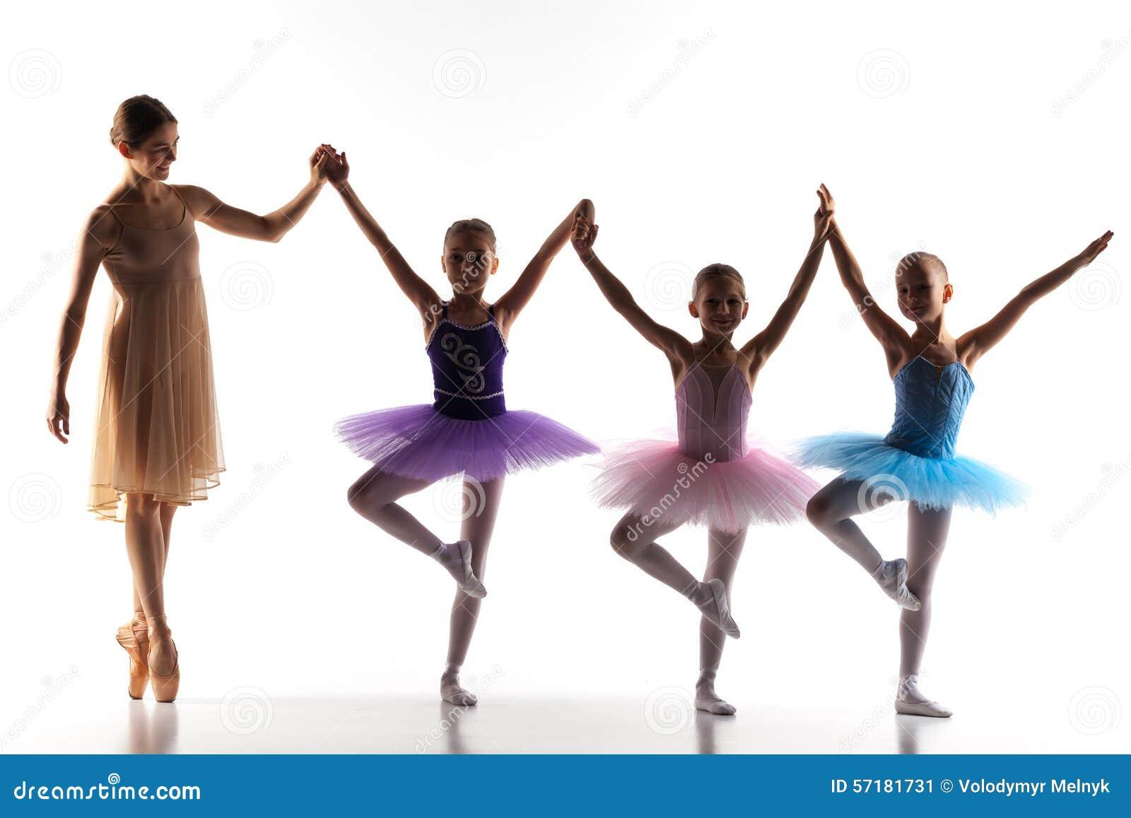 Três bailarinas pequenas que dançam com o professor pessoal do bailado no estúdio da dança