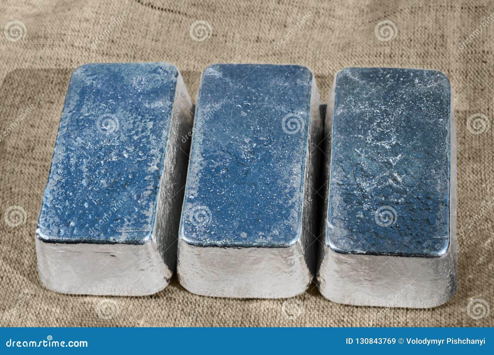 Três barras de prata não marcado contra uma textura áspera de matéria têxtil