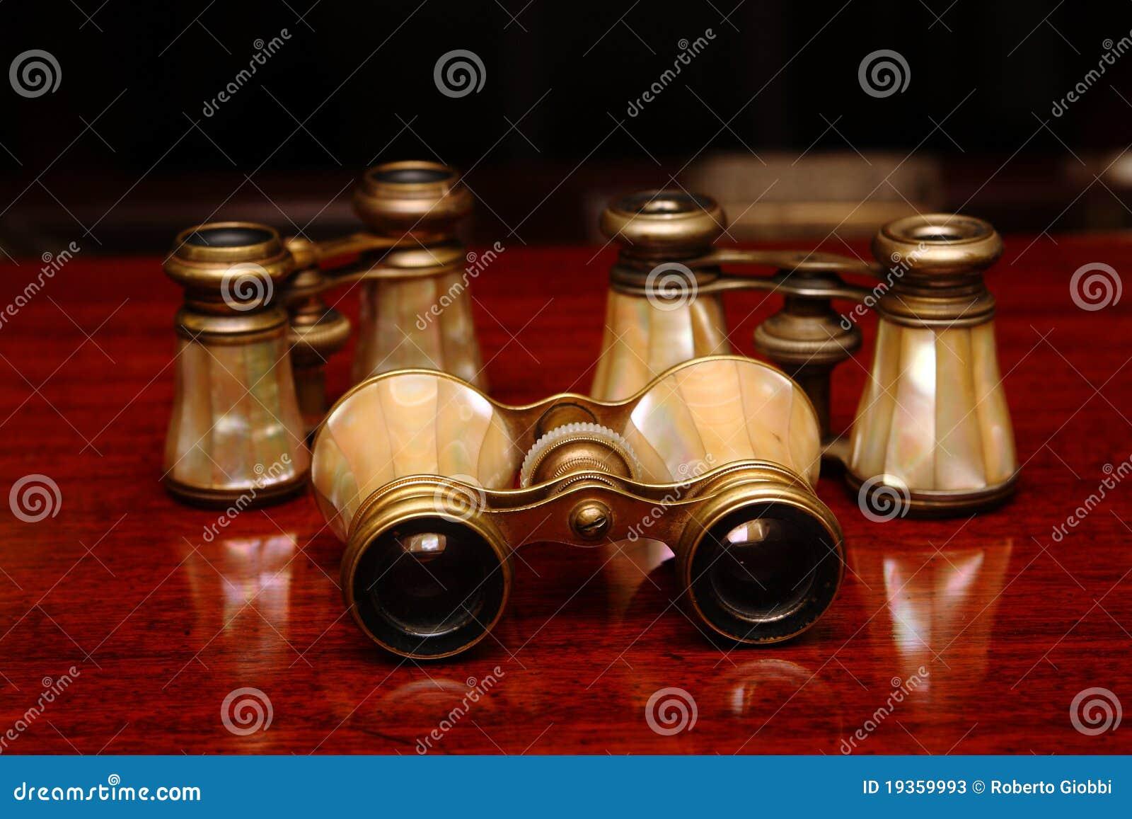 Três binóculos em uma mesa marrom