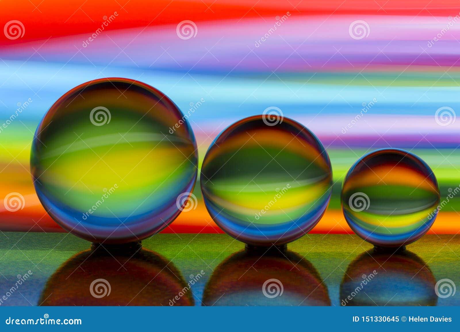Três bolas de cristal de vidro em seguido com um arco-íris da pintura clara colorida atrás deles
