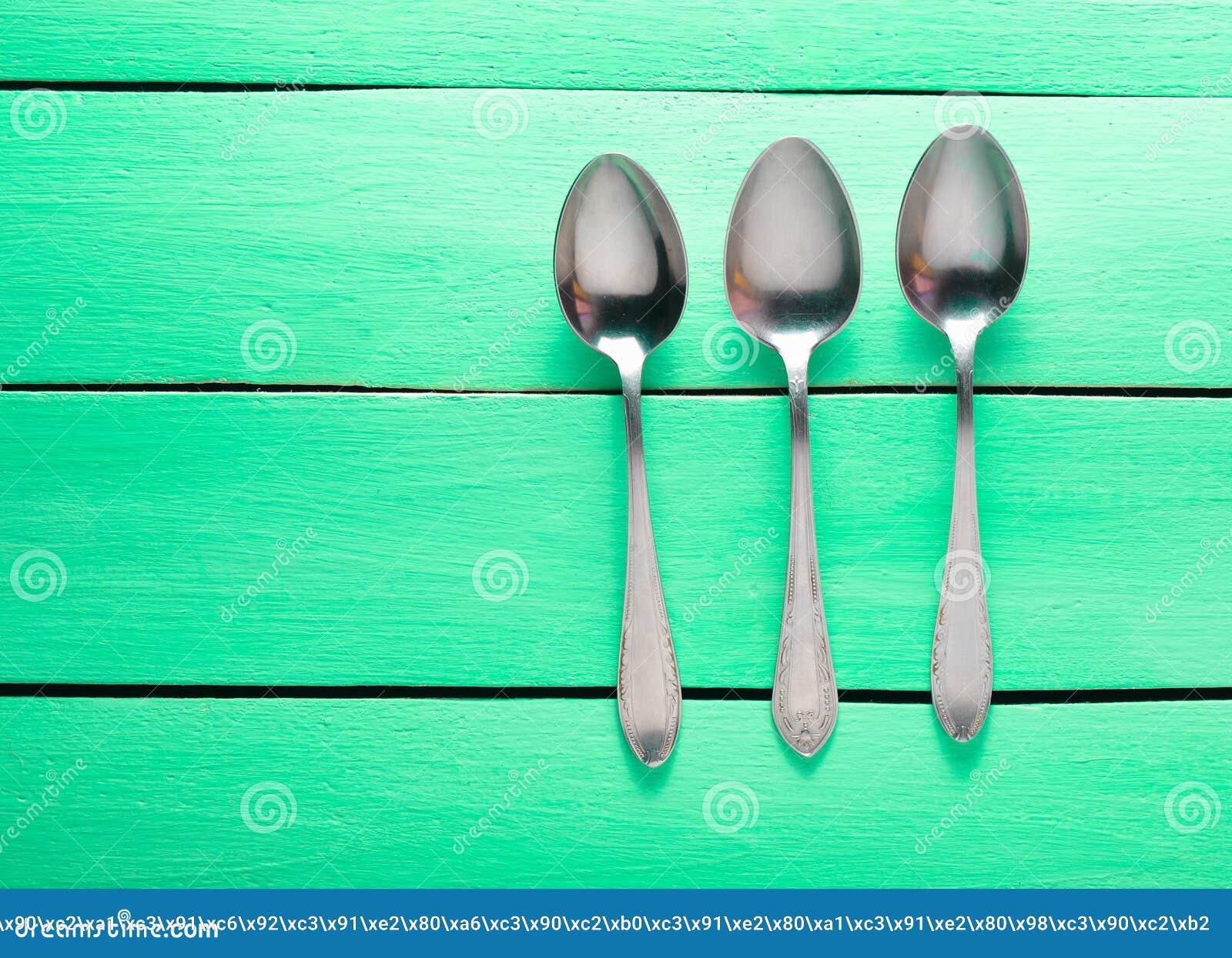 Três colheres de prata em uma tabela de madeira de turquesa Vista superior Copie o espaço