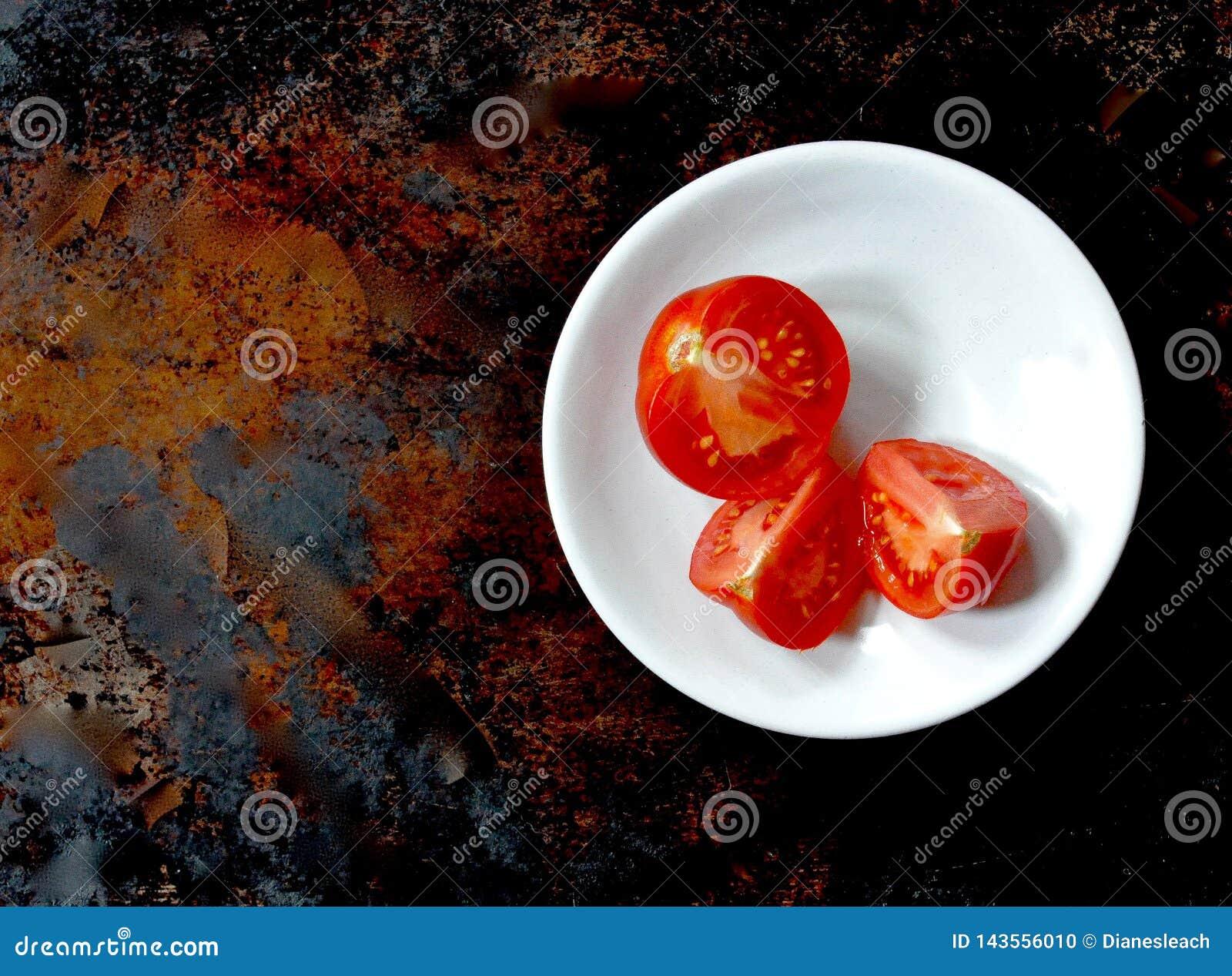 Três cortaram tomates vermelhos em uma bacia branca, direito do centro, fundo marrom