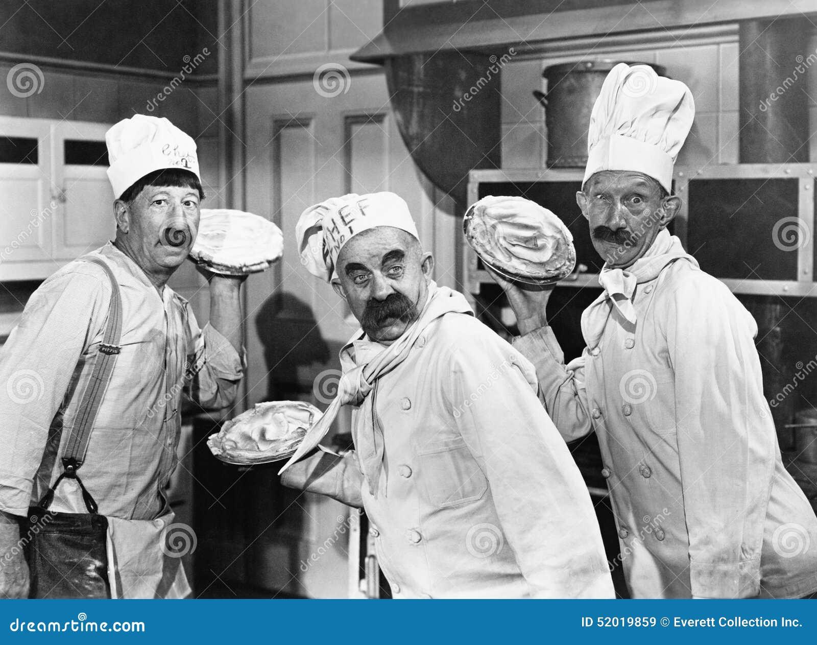 Três cozinheiros chefe que guardam tortas para uma luta na cozinha (todas as pessoas descritas não são umas vivas mais longo e ne
