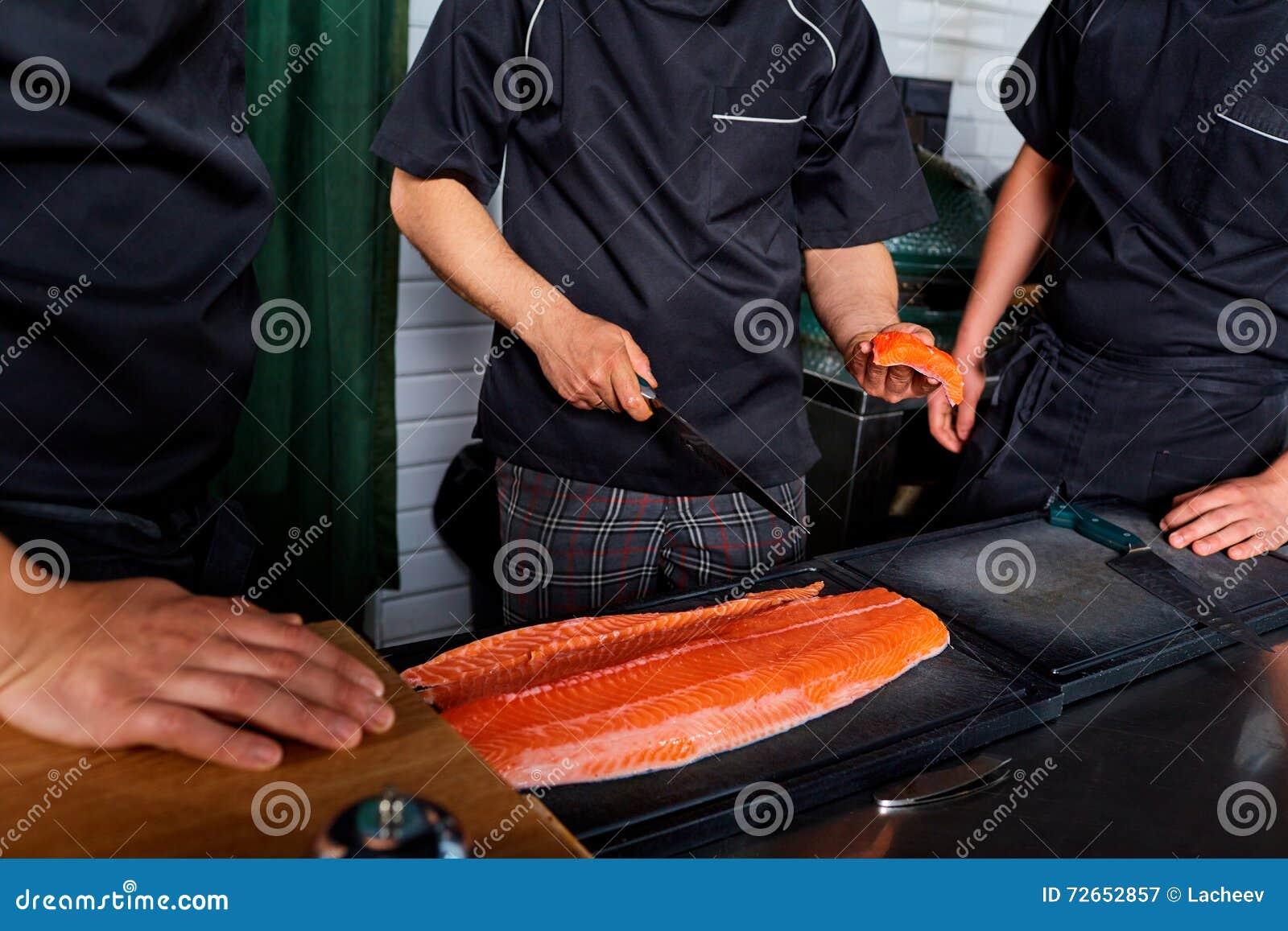 Três cozinheiros dos cozinheiros chefe nos peixes salmon do corte uniforme em faixas com
