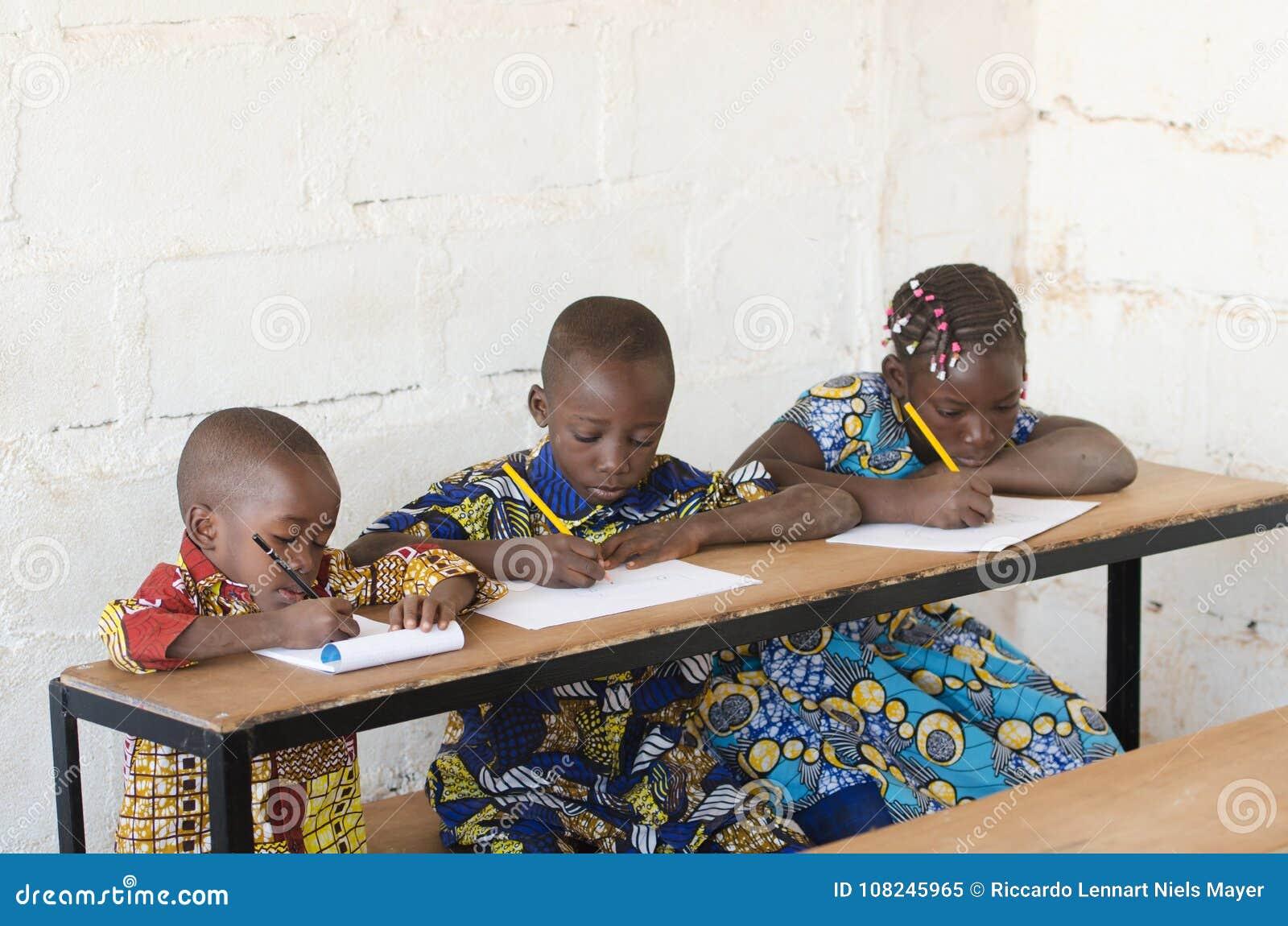 Três crianças africanas bonitas na escola que toma notas durante C
